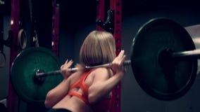 Мышечная женщина разрабатывая в весах спортзала поднимаясь видеоматериал