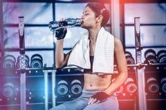 Мышечная женщина сидя на стенде пока питьевая вода Стоковое Изображение RF