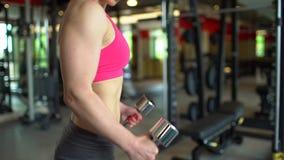 Мышечная женщина спортсмена в розовой верхней части разрабатывая в весах спортзала поднимаясь Девушка фитнеса работая в спортзале акции видеоматериалы