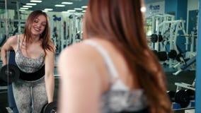 Мышечная женщина спортсмена разрабатывая в весах спортзала поднимаясь Девушка фитнеса работая в спортзале с гантелями сток-видео