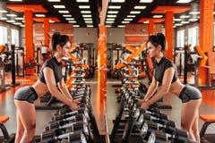 Мышечная молодая женщина с красивым телом делая тренировки с гантелью стоковые фото
