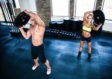 Мышечная разминка человека и женщины на спортзале Стоковое Изображение RF