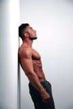 Мышечная склонность человека против стены a Стоковые Фото
