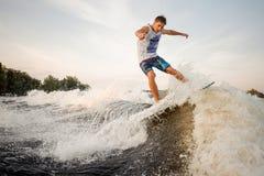 Мышечное и сильное wakesurfer скача и ехать вниз с реки Стоковые Изображения RF