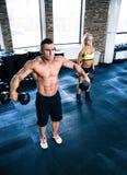 Мышечные гантели человека и женщины пригонки поднимаясь Стоковая Фотография RF