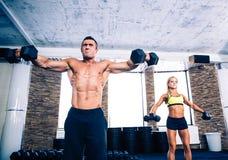 Мышечные гантели человека и женщины пригонки поднимаясь Стоковые Фотографии RF