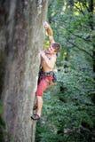 Мышечные подъемы альпиниста утеса на свисая скале Стоковое Изображение