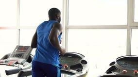 Мышечный Афро-американский человек бежать на третбане в спортзале, разминке, спорте видеоматериал