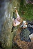 Мышечный альпинист утеса взбирается на стене скалы с веревочкой Стоковые Изображения RF