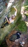 Мышечный альпинист утеса взбирается на стене скалы с веревочкой Стоковые Изображения
