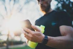 Мышечный бородатый спортсмен проверяя, который сгорели калории на применении smartphone после встречи хорошей разминки внешней на стоковая фотография