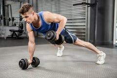 Мышечный делать человека нажимает вверх с гантелями Стоковые Изображения RF