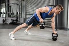 Мышечный делать человека нажимает вверх с kettlebells Стоковое Изображение