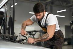 Мышечный механик в coveralls, белая футболка ремонтируя автомобиль стоковое изображение