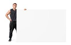 Мышечный молодой человек в sportswear держит сторону огромного пустого знамени изолированного на белой предпосылке Стоковые Изображения RF