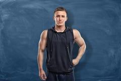 Мышечный молодой человек в sportswear стоит на синей предпосылке Стоковое фото RF