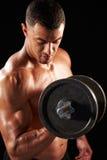 Мышечный молодой человек разрабатывая с тяжелой гантелью Стоковые Изображения RF
