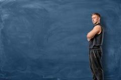 Мышечный молодой человек стоит его пересеченные оружия и смотрит вперед на голубой предпосылке доски стоковое фото