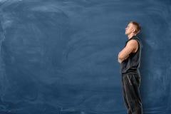 Мышечный молодой человек стоит его пересеченные оружия и смотрит вверх на голубой предпосылке доски стоковое фото rf
