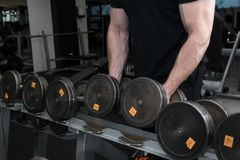 Мышечный парень культуриста держа большие гантели черного листового железа в спортзале Человек с сильной рукой muscles разработка стоковое изображение rf