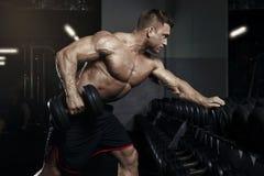 Мышечный парень культуриста делая тренировки с гантелью в спортзале Стоковое Фото
