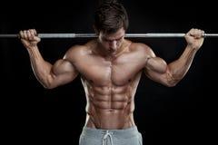 Мышечный парень культуриста делая тренировки с гантелью стоковое изображение rf