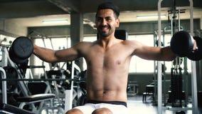 Мышечный сильный молодой человек делая плечи наверху отжимает подниматься с гантелями в спортзале фитнеса сток-видео