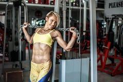 Мышечный спортсмен молодой женщины представляя на спортзале с цепью в руках Стоковое Фото