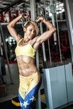 Мышечный спортсмен молодой женщины представляя на спортзале с цепью в руках Стоковая Фотография RF