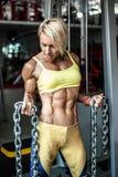 Мышечный спортсмен молодой женщины представляя на спортзале с цепью в руках Стоковая Фотография