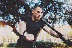 Мышечный спортсмен работая trx нажимает вверх снаружи в солнечном парке Подходящая без рубашки мужская модель фитнеса в тренировк Стоковое Изображение