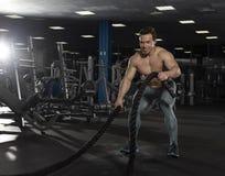 Мышечный спортсмен с сражением ropes тренировка в современном ce фитнеса Стоковое фото RF