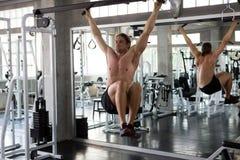 Мышечный человек делая вытягивать вверх на баре и нагнетать вверх 6 пакетов подбрюшных на спортзале разминка, тренировки, трениро стоковое фото