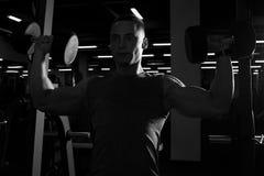 Мышечный человек делая прессу гантели надземную в спортзале силуэт Стоковые Изображения