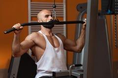 Мышечный человек делая тяжеловесную тренировку для задней части Стоковое Изображение