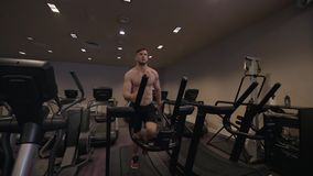 Мышечный человек делая cardio тренировку на третбане в здоровом замедленном движении клуба стоковые изображения rf