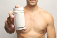 Мышечный человек держа лекарства в бутылке стоковые изображения rf