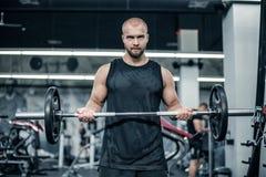 Мышечный человек разрабатывая в спортзале делая тренировки со штангой на бицепсе, сильном мужчине стоковое изображение