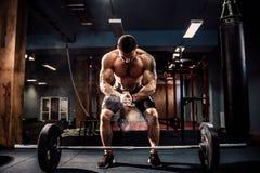 Мышечный человек фитнеса подготавливая к deadlift штангу над его головой в современном фитнес-центре Функциональная тренировка Стоковые Фотографии RF
