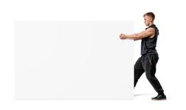 Мышечный человек держа ясное белое табло с его кулаками Стоковое Фото