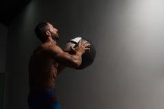 Мышечный человек делая тренировки шарика медицины стоковое изображение