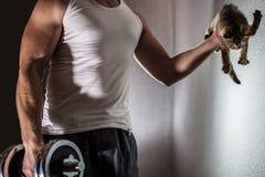 Мышечный человек делая тренировку с гантелью в одной руке и в его другой руке милый котенок Стоковые Фотографии RF