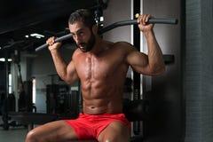 Мышечный человек делая тяжеловесную тренировку для задней части Стоковое Изображение RF