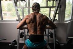 Мышечный человек делая тяжеловесную тренировку для задней части Стоковые Фотографии RF