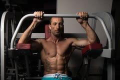 Мышечный человек делая тяжеловесную тренировку для задней части Стоковое Фото