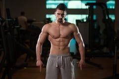 Мышечный человек изгибая мышцы в спортзале Стоковые Изображения