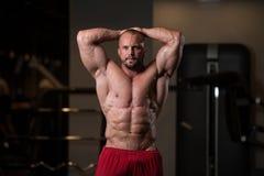 Мышечный человек изгибая мышцы в спортзале Стоковые Изображения RF
