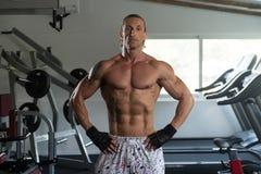 Мышечный человек изгибая мышцы в спортзале Стоковое Фото