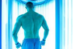 Мышечный человек на солярии в салоне красоты Стоковые Изображения