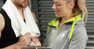 Мышечный человек обсуждая с спортсменкой видеоматериал